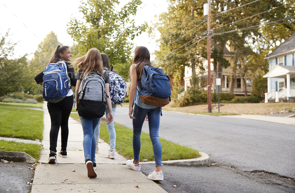 Four young teen girls walking to school together, back view - Stock Photo - Images
