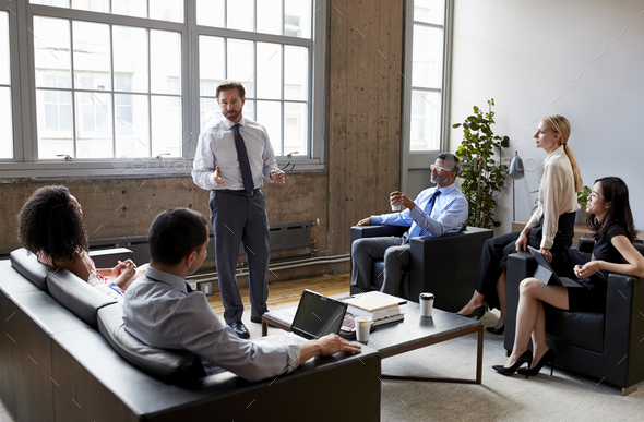 Businessman presenting to colleagues at an informal meeting - Stock Photo - Images