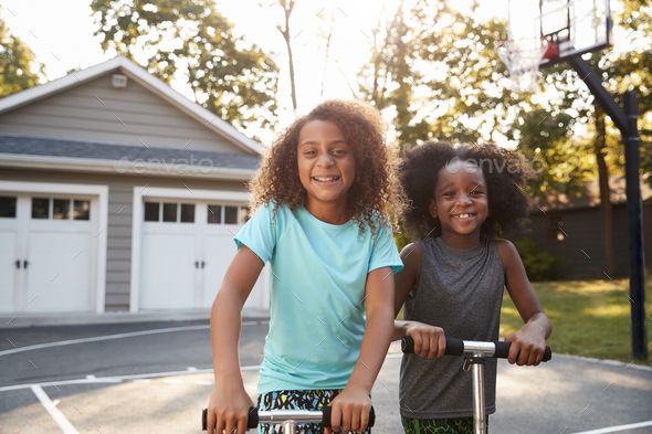 Brother And Sister Riding Scooters On Driveway At Home - Stock Photo - Images