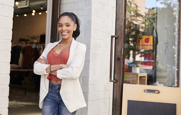 Young Hispanic businesswoman smiling to camera outside her shop - Stock Photo - Images