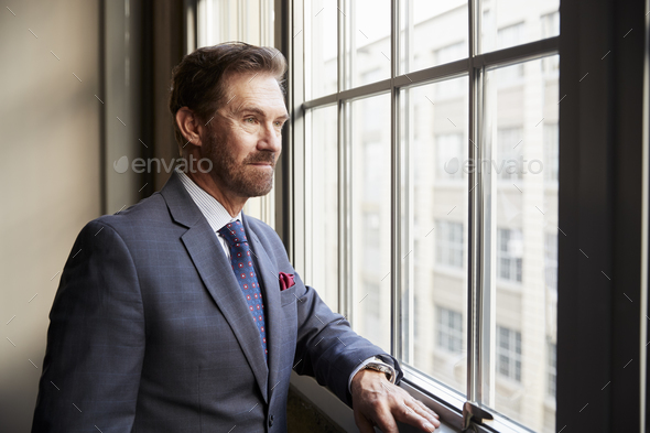 Senior white businessman looking out of window - Stock Photo - Images