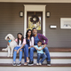 Family With Children And Pet Dog Sit On Steps Of Home - PhotoDune Item for Sale