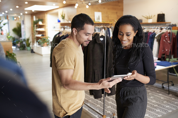 Smiling couple using tablet computer in a clothes shop - Stock Photo - Images