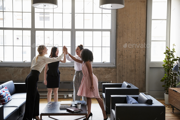Female colleagues high five at a motivational meeting - Stock Photo - Images