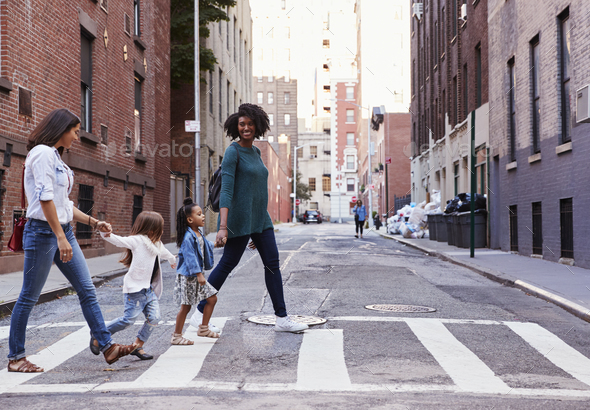 Two mother friends with two daughters crossing the road - Stock Photo - Images