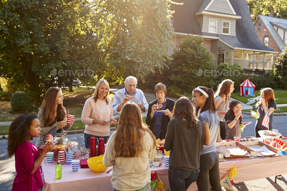 Neighbours talk and eat around a table at a block party - Stock Photo - Images