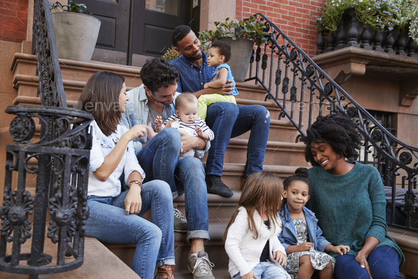 Two families with kids sitting on front stoops - Stock Photo - Images