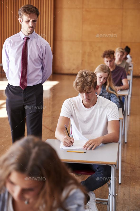 Teenage Students Sitting Examination With Teacher Invigilating - Stock Photo - Images