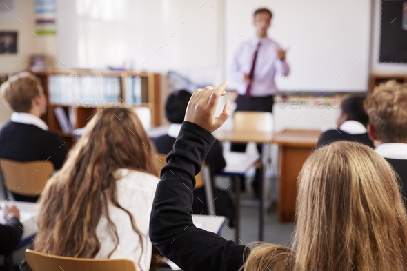 Female Student Raising Hand To Ask Question In Classroom - Stock Photo - Images