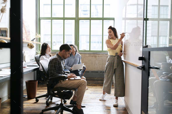 Woman using whiteboard in a small team meeting - Stock Photo - Images