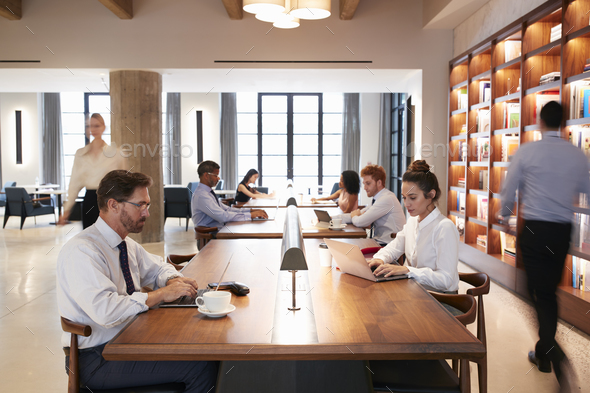 Colleagues at desks in a busy open plan office, close up - Stock Photo - Images