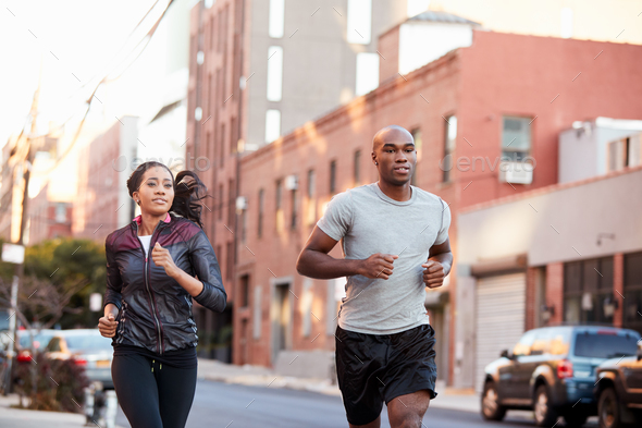 Young black couple jogging in Brooklyn street, close up - Stock Photo - Images