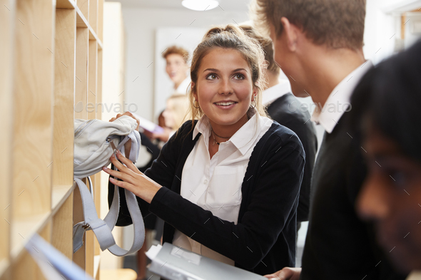 Teenage Students Putting Away Books After Class - Stock Photo - Images