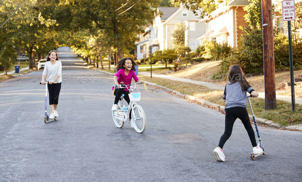 Three girls riding on scooters and a bike in the street - Stock Photo - Images