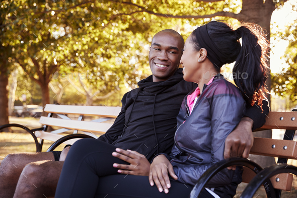 Young black couple sitting on bench in Brooklyn park - Stock Photo - Images