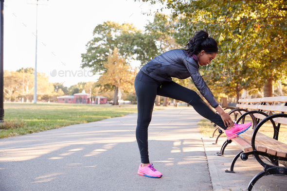 Young black woman stretching on bench in a park, full length - Stock Photo - Images