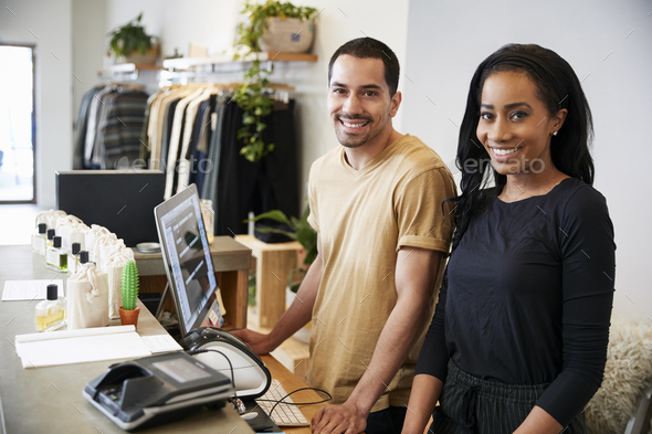 Smiling colleagues behind the counter in clothing store - Stock Photo - Images