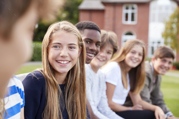 Group Of Teenage Students Sitting Outside School Buildings - Stock Photo - Images