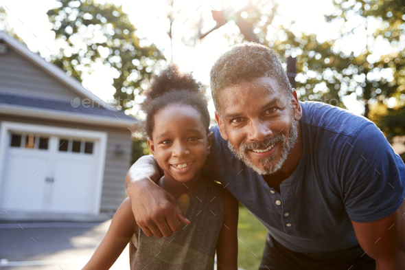 Portrait Of Father And Son Playing Basketball On Driveway - Stock Photo - Images