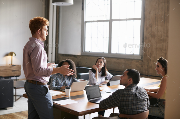 Young man standing to address colleagues at a work meeting - Stock Photo - Images