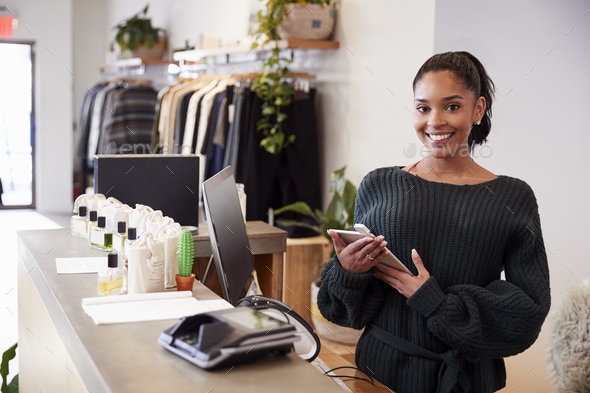 Female assistant smiling from the counter in clothing store - Stock Photo - Images