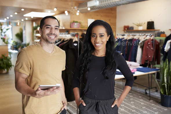 Young couple with tablet smiling to camera in a clothes shop - Stock Photo - Images