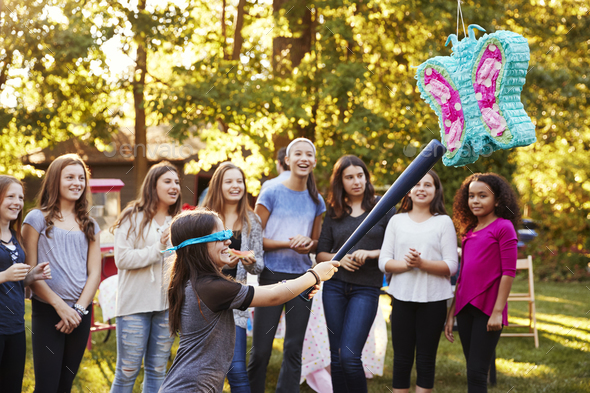 Friends watch a young girl hitting a pi–ata on her birthday - Stock Photo - Images