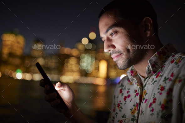 Man Using Mobile Phone At Night With City Skyline In Background - Stock Photo - Images