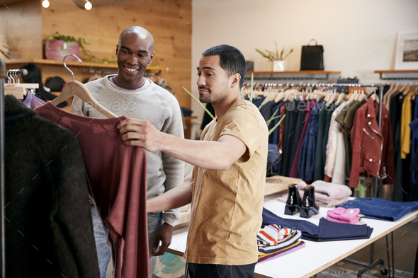 Two male friends looking at clothes in a clothes shop - Stock Photo - Images