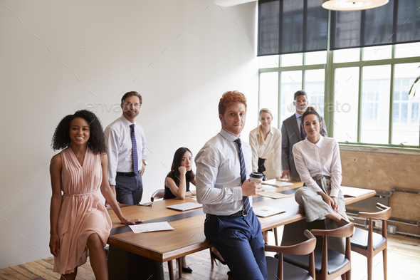 Young professionals in a meeting room looking to camera - Stock Photo - Images