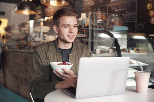 Young Man Using Laptop In Cafe Whilst Eating Breakfast - Stock Photo - Images