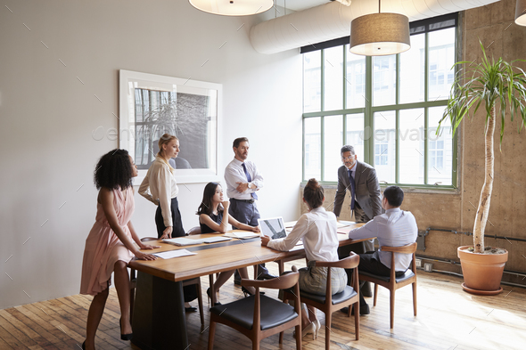 Young professionals around a table at a business meeting - Stock Photo - Images