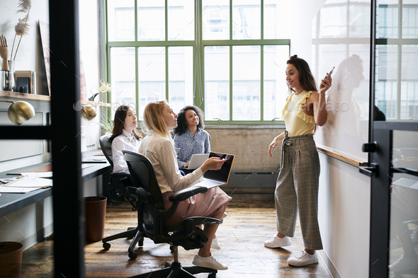 Woman pointing at whiteboard in a meeting with female team - Stock Photo - Images