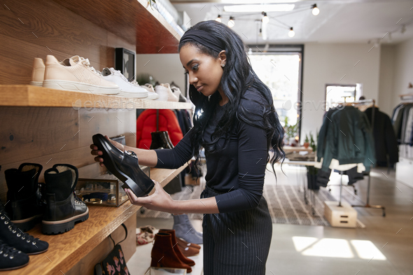 Young black woman looking at shoes on display in a shop - Stock Photo - Images