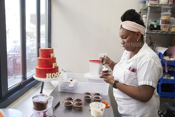 Young black woman frosting cakes at a bakery - Stock Photo - Images
