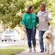 Senior Couple Walking Dog Along Suburban Street - PhotoDune Item for Sale