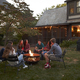 Teenagers sit talking around a fire pit in a garden at dusk - PhotoDune Item for Sale