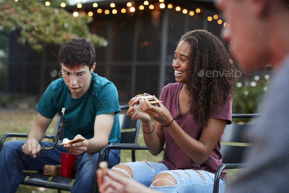 Teenage black girl making sÕmore with friends at a fire pit - Stock Photo - Images