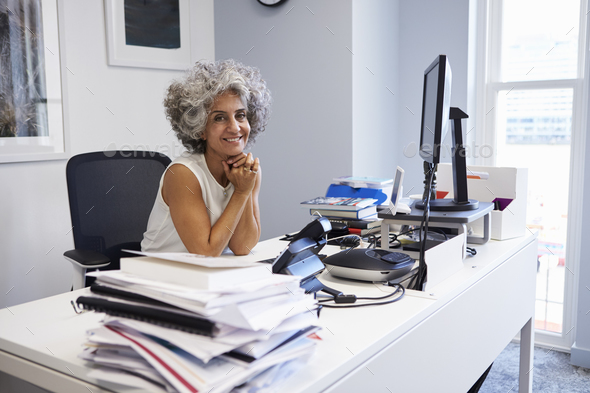 Middle aged businesswoman smiling to camera in her office - Stock Photo - Images