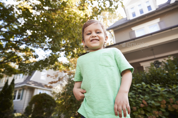 Portrait Of Young Boy Playing In Garden At Home Stock Photo by monkeybusiness