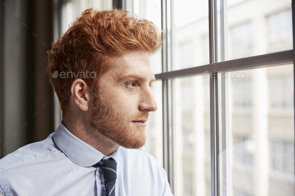 Young red haired bearded businessman looking out of window - Stock Photo - Images