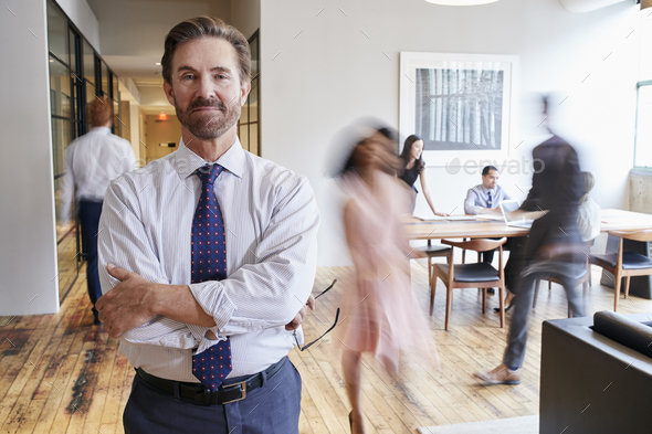 Portrait of middle aged white man in a busy modern workplace - Stock Photo - Images