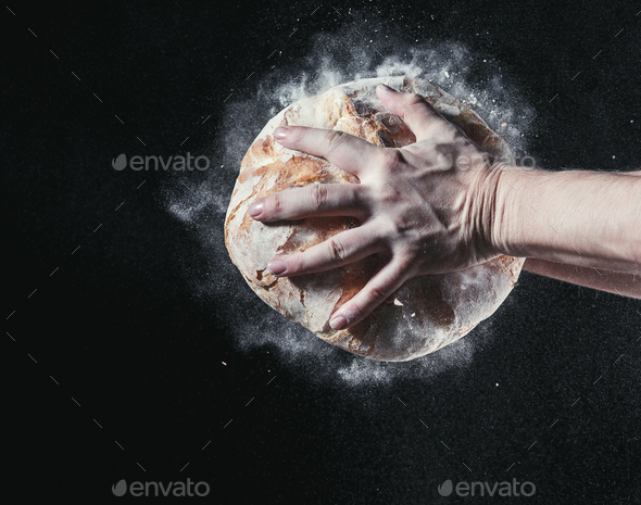 Closeup of male hands put fresh bread on black background with copy space for your text - Stock Photo - Images