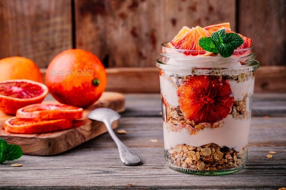 healthy breakfast  glass jar yogurt parfait with homemade granola and blood orange - Stock Photo - Images