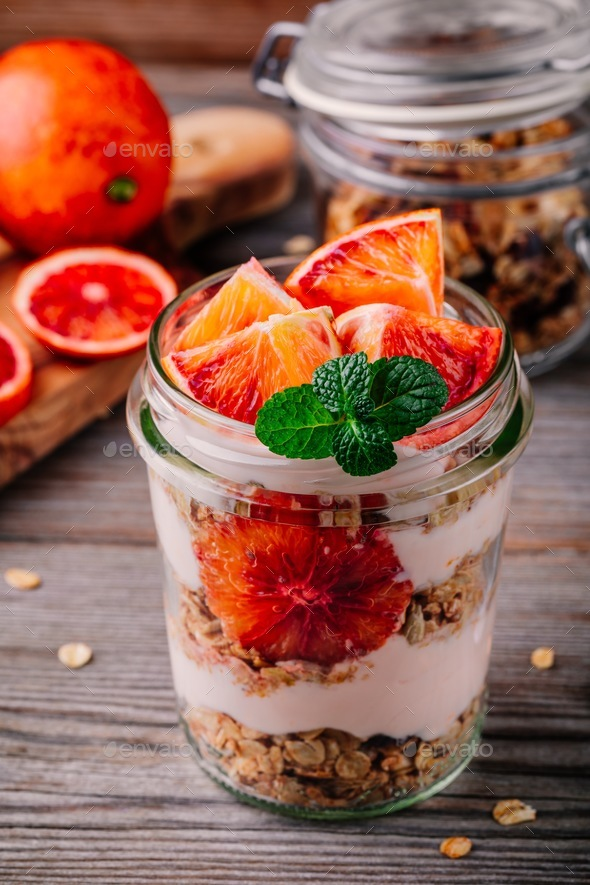 healthy breakfast  glass jar yoghurt parfait with homemade granola and blood orange - Stock Photo - Images