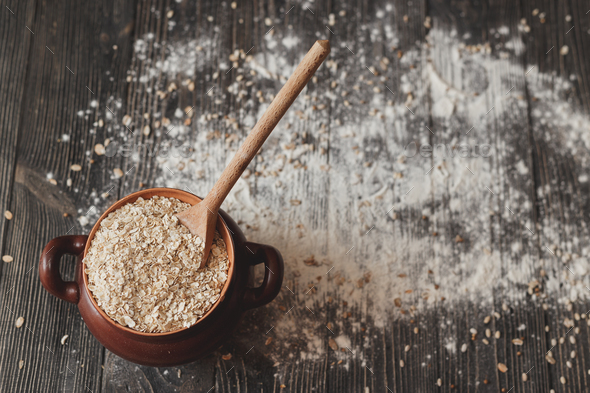 Pot with a spoon full of cereals and on rustic background. Top view - Stock Photo - Images