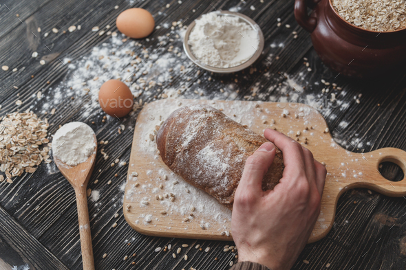 Close-up of men's hands on black bread with flour powder. Baking and patisserie concept. - Stock Photo - Images