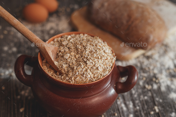 Pot filled with oatmeal on the table  a spoon, eggs and bread - Stock Photo - Images