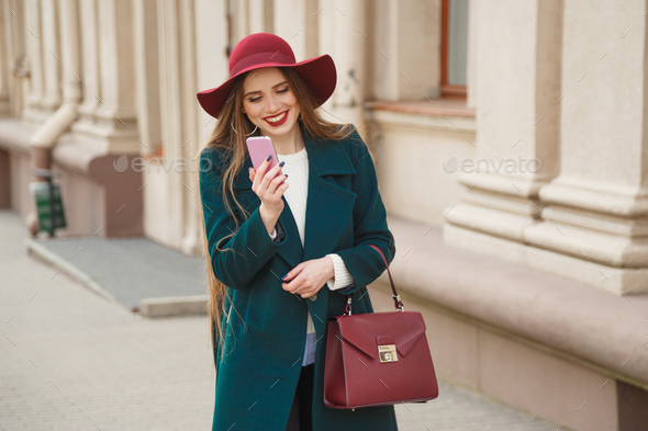 Beautiful stylishly dressed young woman receives a phone call - Stock Photo - Images