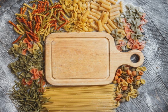 Mixed raw pasta with wooden board on old black  desk - Stock Photo - Images
